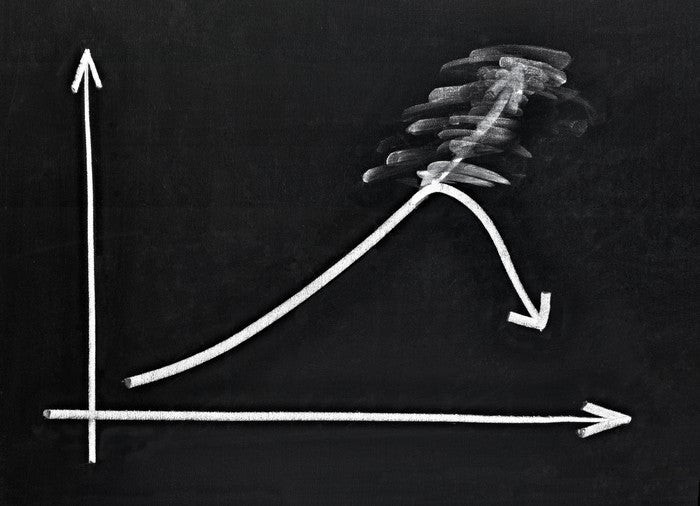 A chalkboard drawing of a stock chart, with an arrow going up being erased, then pointing back down