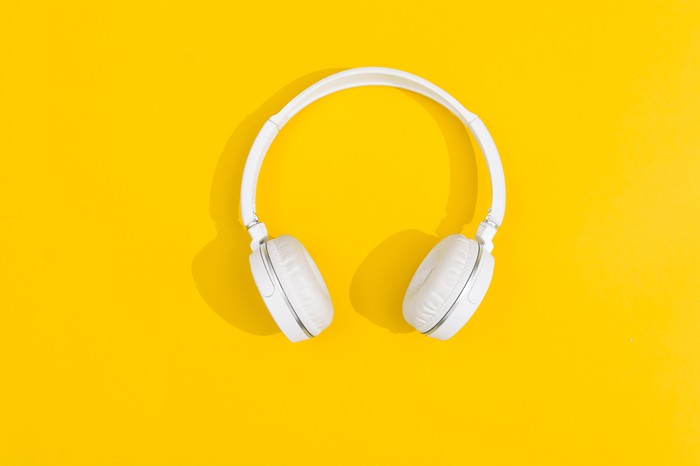 White over-the-ear headphones with a yellow background.