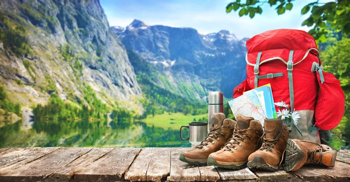 Hiking footwear and accessories against a backdrop of cliffs and forested lake.