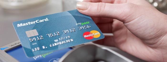 A hand using a payment card with a reader.