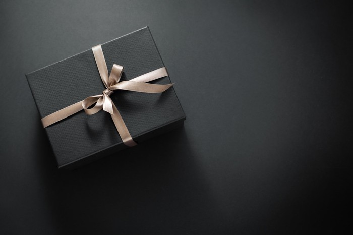 A gift wrapped in dark paper on a dark background.