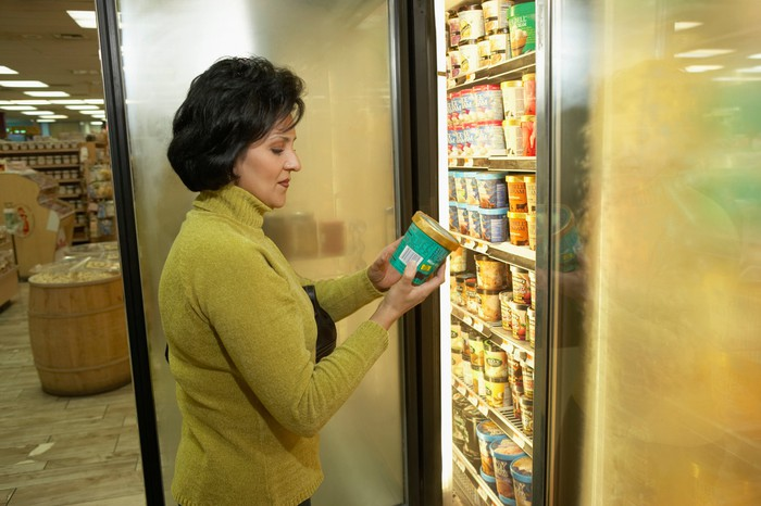 A shopper looking at frozen goods in a supermarket.