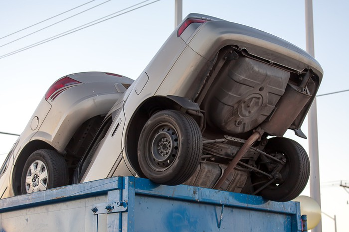 Clunker cars in a dumpster.