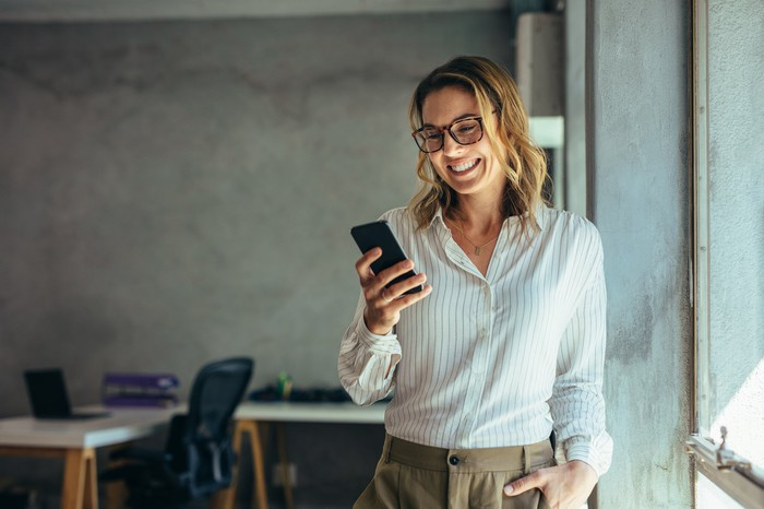 Woman smiling while looking at mobile phone in her hand