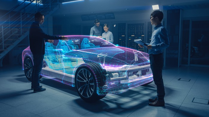Three designers are working on an augmented reality car.