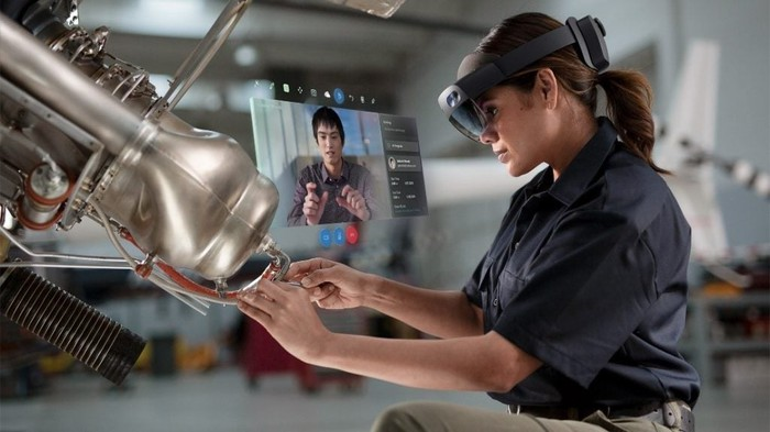 The illustration shows the Microsoft HoloLens 2 used by a factory worker when she produces a part.