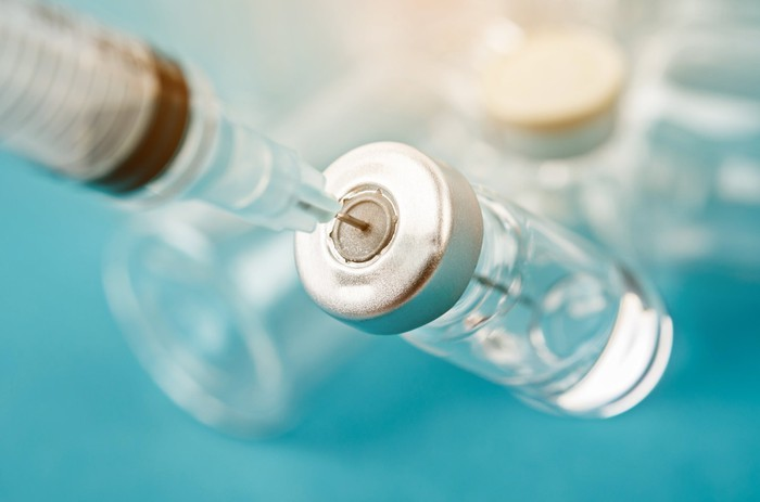 Vaccine bottle and a syringe, against a blue background