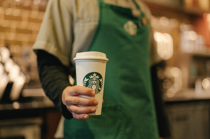 A Starbucks employee, wearing a green apron, holds a cup with the Starbucks logo printed on the side.