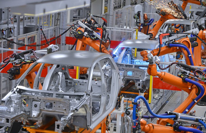 auto assembly line with robots welding on vehicle frames