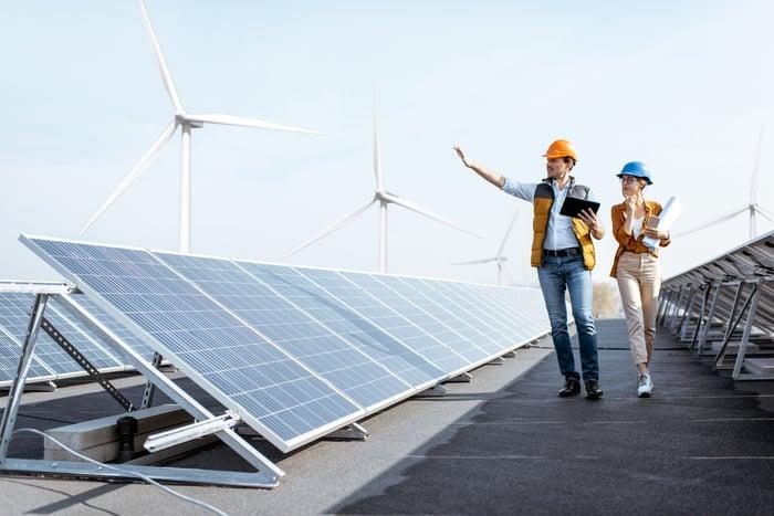 Engineers walk beside solar panels.
