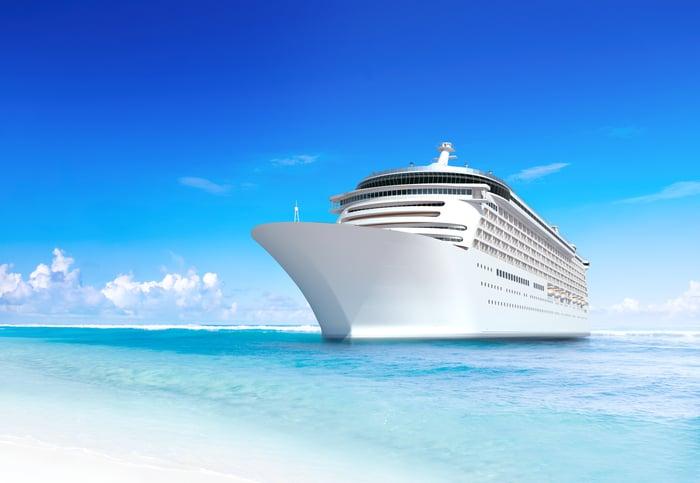 Cruise ship docked off a sandy beach.