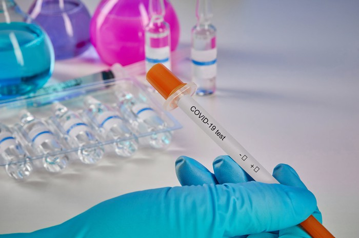 A hand in a blue glove holds a tube labeled as a COVID-19 test