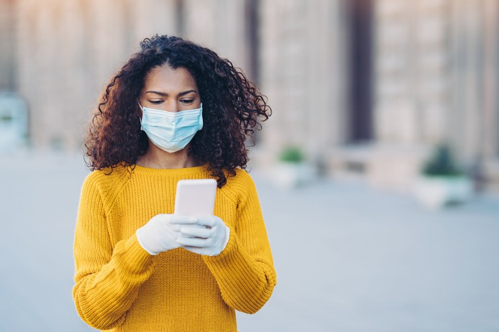 Woman looking at her smartphone while wearing a medical mask and gloves and standing outside.