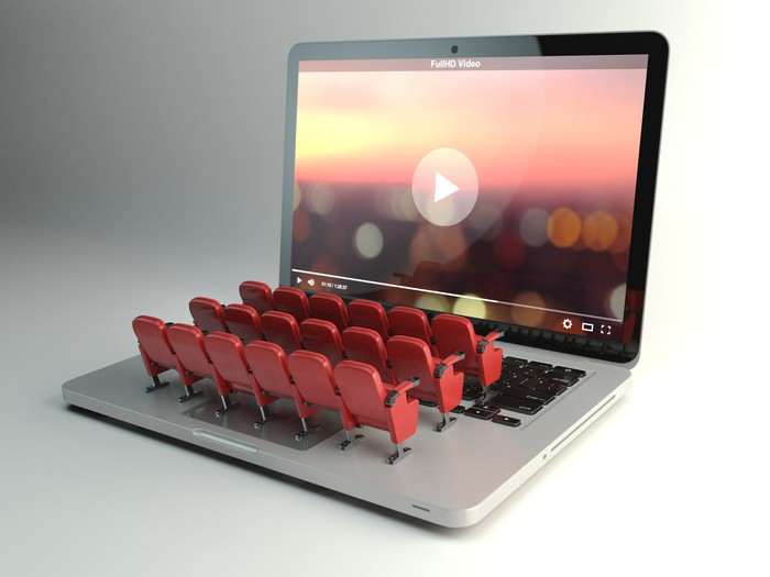 Minature theater seats lined up on a keyboard face a laptop screen preparing to play a movie.