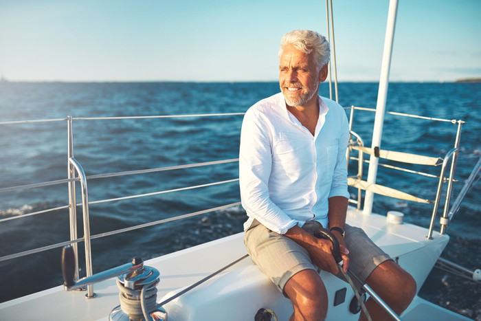 A retiree sits on his sailboat in the ocean.