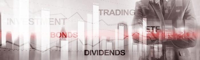 Investing-related words, including dividends, bonds, and ETFs, written on a wall.