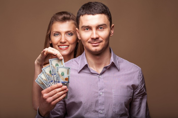 A young man and woman holding a handful of cash.
