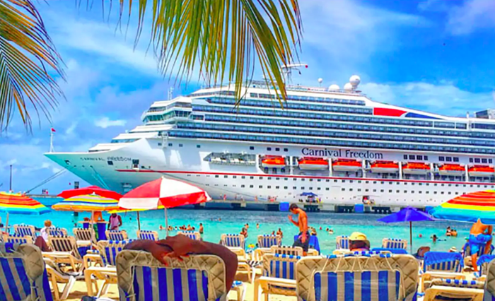 Carnival Freedom docked near a private beach.