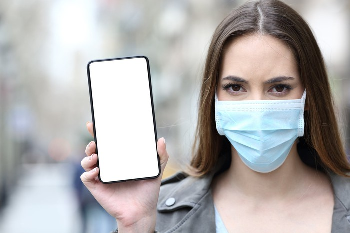 A young woman wears a face mask and brandishes her smartphone while looking at the camera.