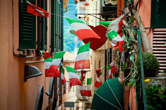 Italian flags hanging in a crowded street.