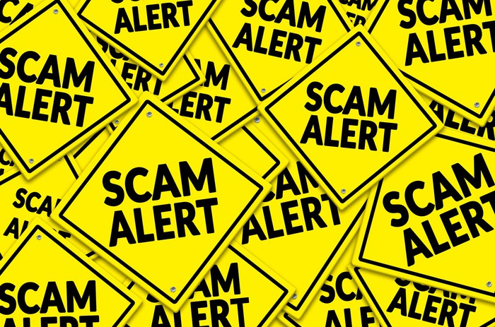 A sea of criss-crossed yellow danger signs that each say scam alert.