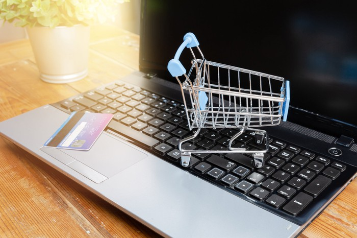 Credit card and shopping cart on laptop