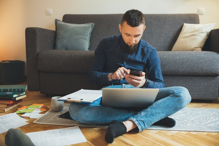Man sitting on floor holding phone with laptop and clipboard in lap