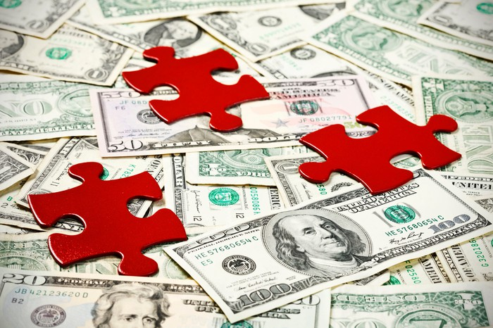 Three red jigsaw puzzle pieces on a pile of cash