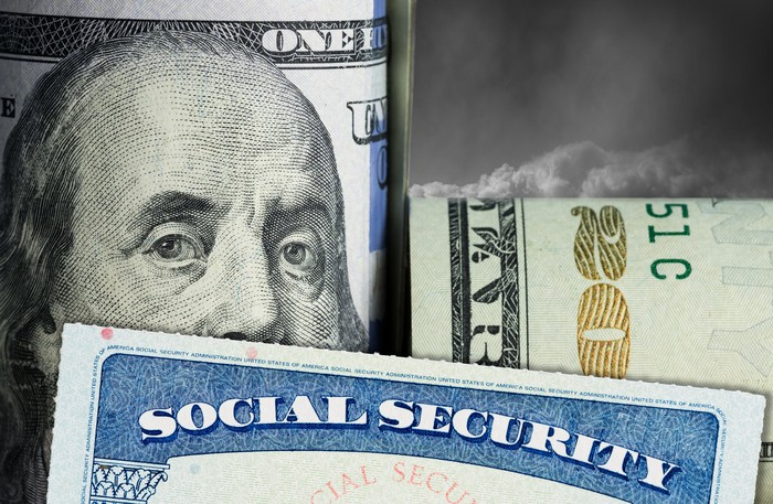 Social Security card with a rolled up one hundred dollar bill and twenty dollar bill behind it