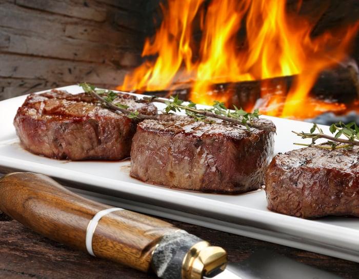 Three beef steaks on a platter beside a wood fire