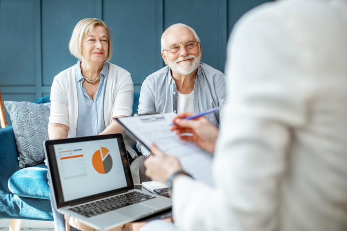 A retired couple discusses their portfolio with a financial adviser.