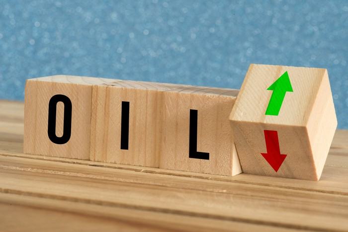 "Three wooden blocks spelling the word ""oil"" with a fourth block using up and down arrows for the rise or fall of oil prices."