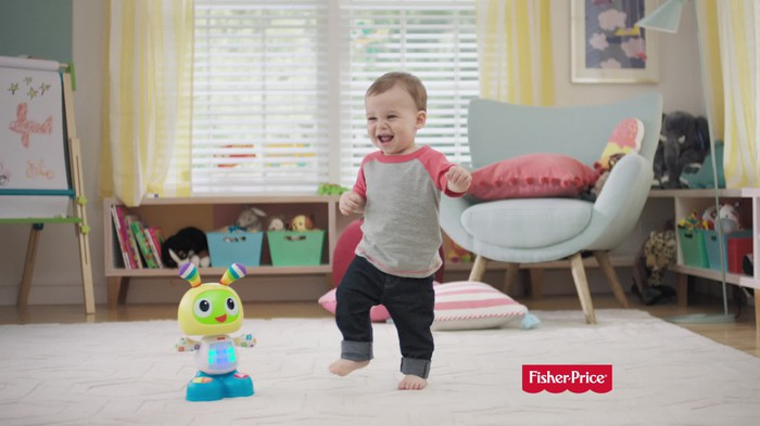A toddler playing with a toy made by Mattel's Fischer Price.