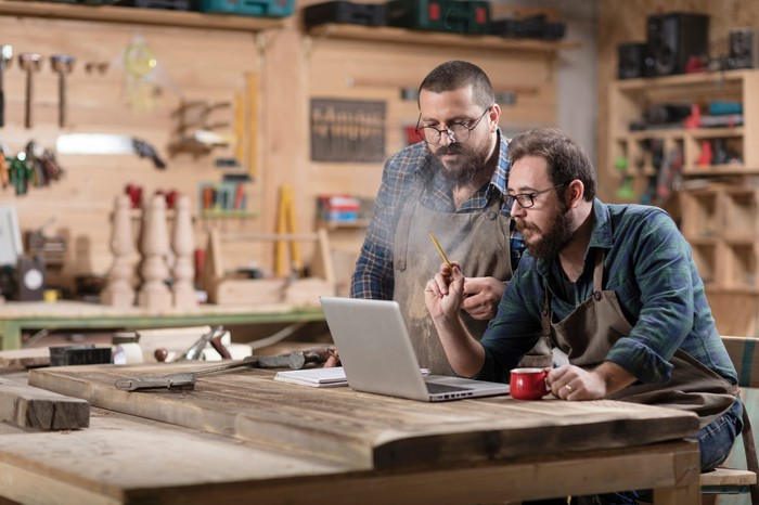 Two men looking at a laptop on a table inside a small workshop