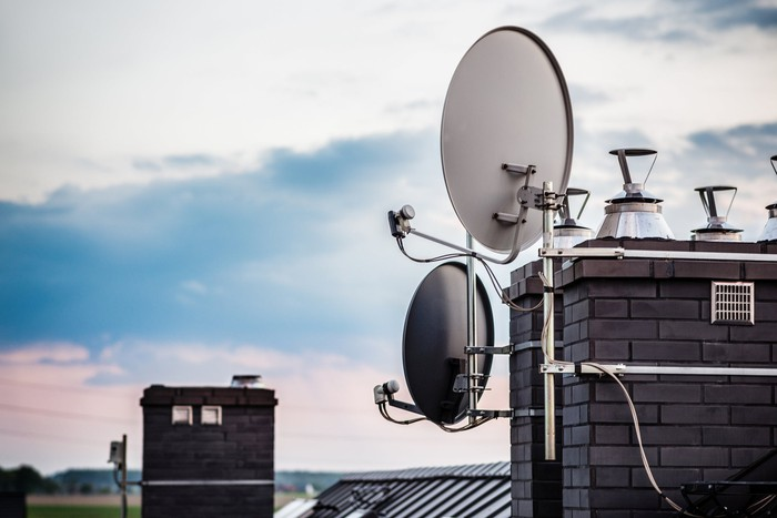 Two satellite dish receivers attached to a modern, slate-grey brick chimney.