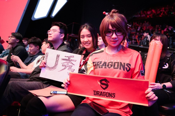 An Overwatch fan at a league match holding up a sign and wearing a team jersey for the Shanghai Dragons.