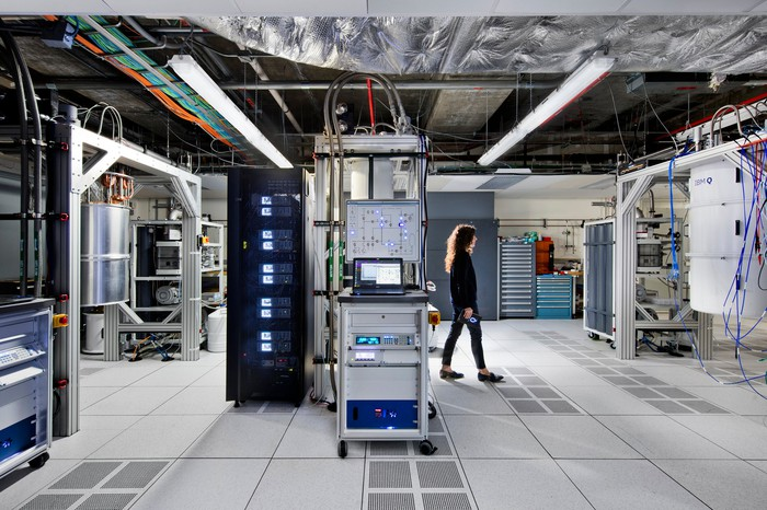 A woman walks through a modern data center, where many of the hardware racks are filled with quantum computing equipment.
