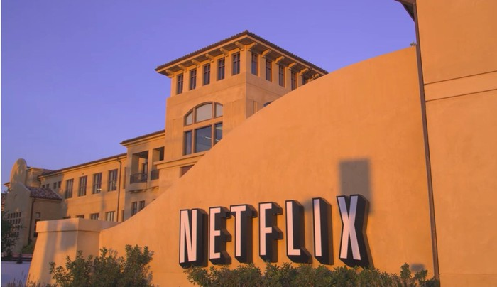 A white Netflix logo on a beige stucco wall outside the company's headquarters in Los Gatos, California.