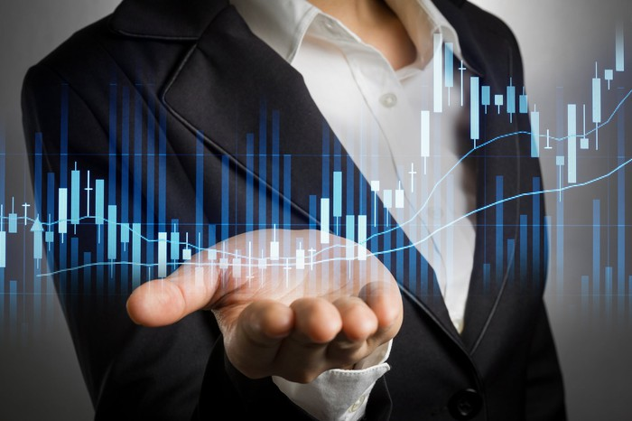 Woman in suit with hand out superimposed over a stock chart