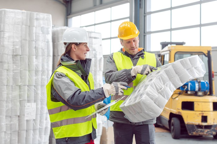 Workers at a warehouse handling large volumes of toilet paper.