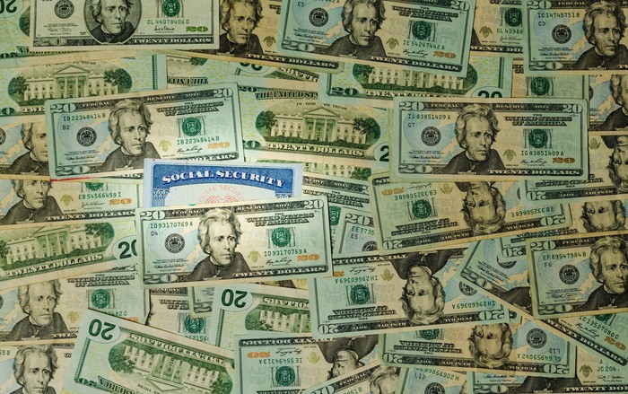 Social Security card sticking out of a pile of 20-dollar bills