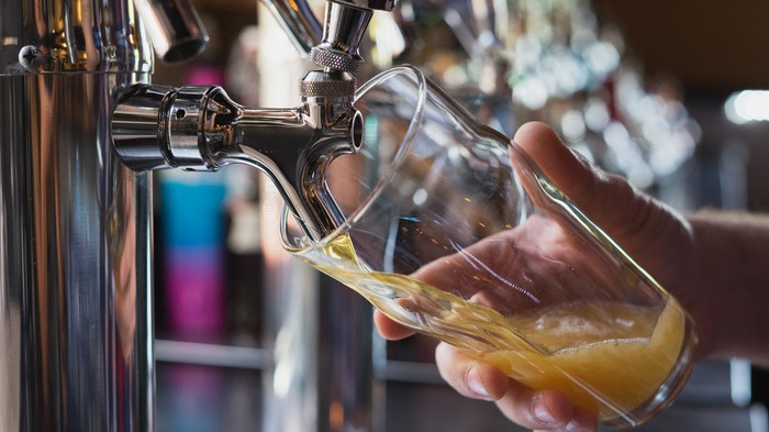 A bartender pours beer into a glass from the tap.