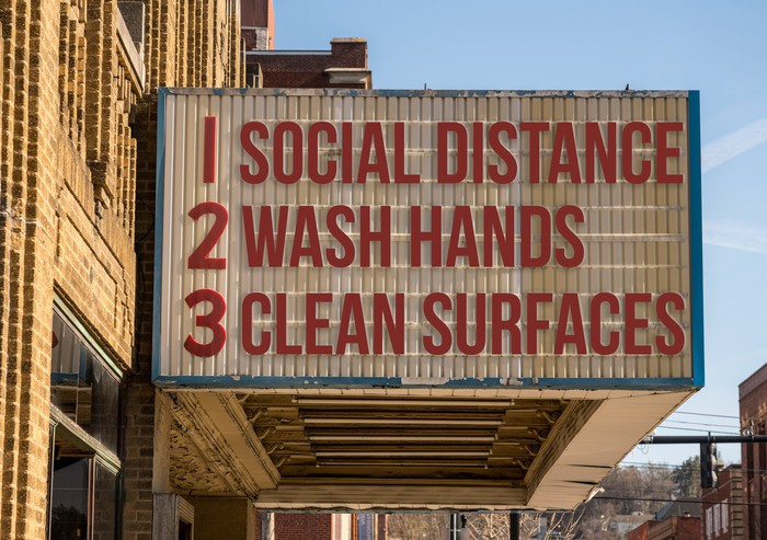 Photo of a theater marquee showing 3 ways to stay safe in the coronavirus era: Social distance, wash hands, clean surfaces.