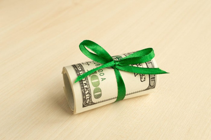 A roll of hundred dollar bills wrapped in a green ribbon.