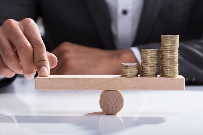 A man holding one side of a balance beam with his finger offsetting coins on the other side