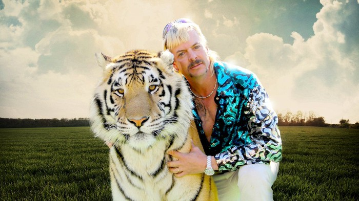 A man with his arms around a tiger, sitting in a field.