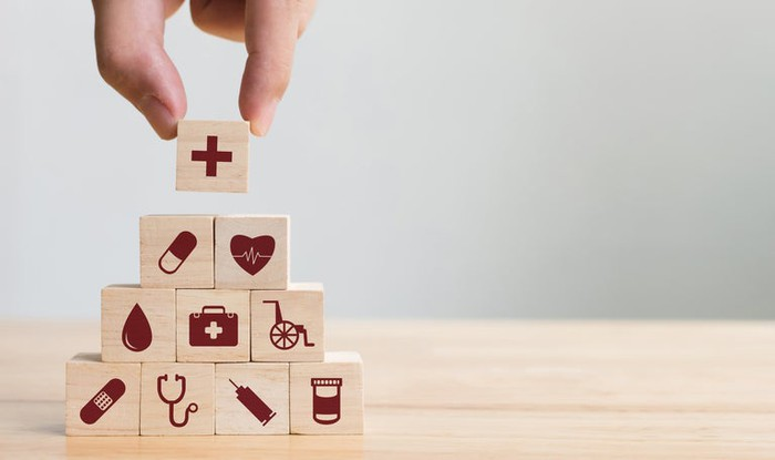 A hand placing the last block on a pyramid of blocks, each with a medical industry icon on its face.