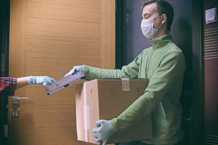 A man wearing a mask delivering a package to a person wearing gloves.