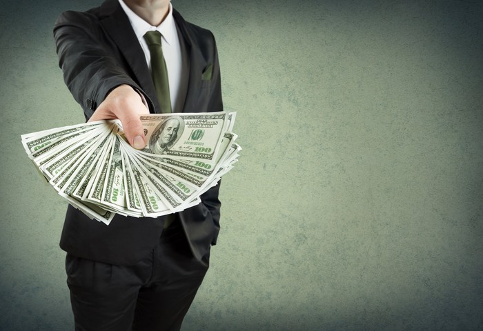 A person in a business suit holding $100 bills in an outstretched arm.