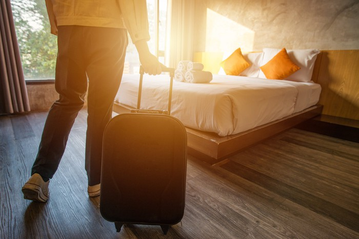 A person pulling a suitcase into a hotel room with the sun shining through the window.